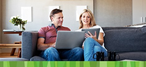 man and woman sitting on couch looking at checking account online
